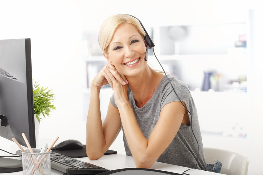 Portrait of a beautiful customer representative with headset smiling during a telephone conversation.